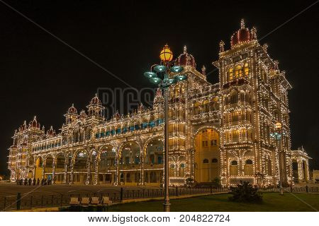 Mysore India - October 27 2013: Sound and light show illuminates Mysore Palace when dark late evening. Frontal view shot from Northeast corner. Music band in photo.