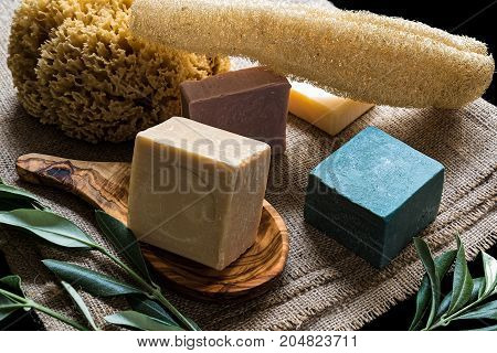 Various colored olive oil soaps and natural sponges on sackcloth