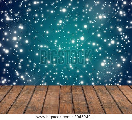 Empty wooden deck on a blue winter background with flying flakes of snow. Christmas background. Empty space for Your subject.