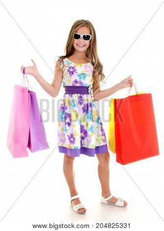 Adorable little girl child in sunglasses holding shopping colorful paper bags isolated on a white