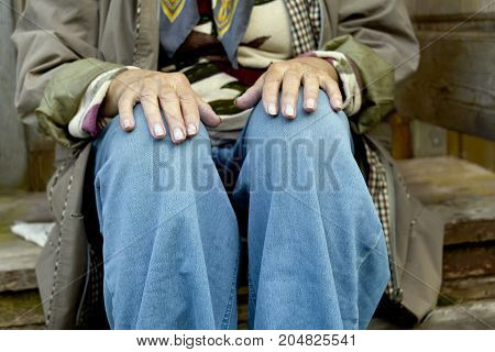 Woman sitting with hands on the knees on the wooden steps outdoor cropped photo