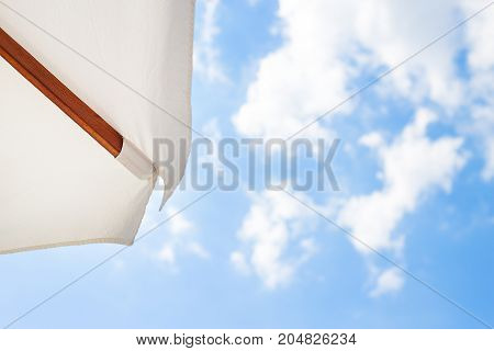 White umbrella-view from above on a beautiful blue sky.
