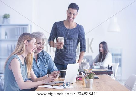 Two young women working together on one laptop at a white office