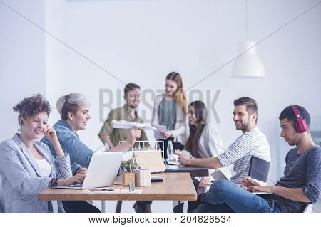 White-haired woman holding handmade paper plane while her colleagues sit with earphones