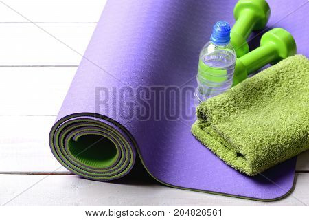 Barbells Near Water Bottle And Soft Towel On Yoga Mat