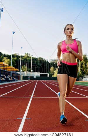 Sporty fitness woman jogging on red running track in stadium. Training summer outdoors on running track line with green trees on background. Sport, healthy lifestyle concept. Front view