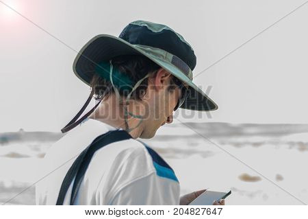 Young Caucasian man with hat checking his mobile phone outside.