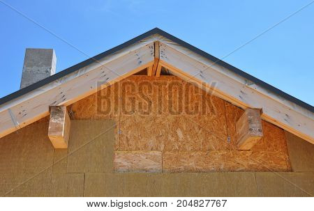 Install on attic roof rock wall insulation with unfinished soffits and fascia boards. House wall insulation.