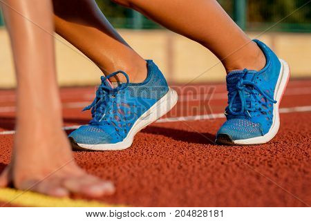 Close-up of woman's legs in blue sneakers on start before jogging. Red treadmill at the stadium