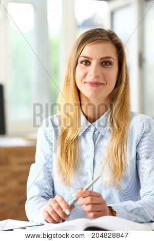 Beautiful smiling girl at workplace hold silver pen looking in camera. White collar worker at workspace modern lifestyle client offer startup project irs audit student study creative discussion