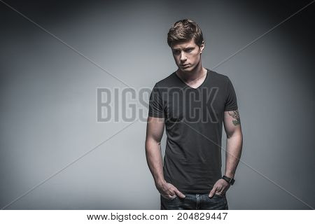 Upset young man is thinking about his problems. He is standing and putting hands in his jeans pockets. Portrait. Isolated and copy space in left side