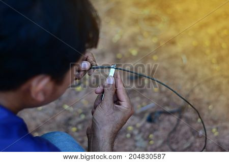 the man peeling the copper wire skin