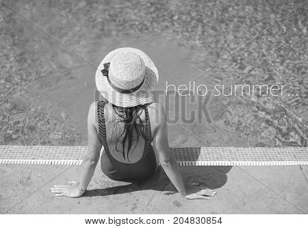 Beautiful girl in a swimsuit near a blue pool - inscription hi summer, black and white photo.