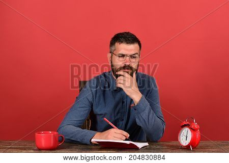 Man With Beard, Glasses Writes In Notebook On Red Background