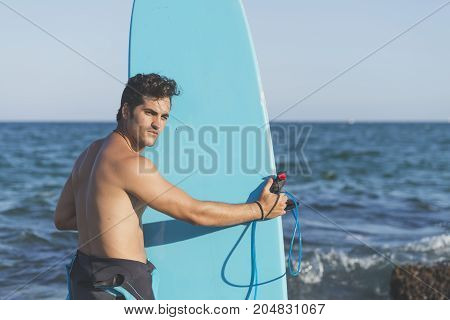 Surfer holding his blue surfboard ( LIFESTYLE )