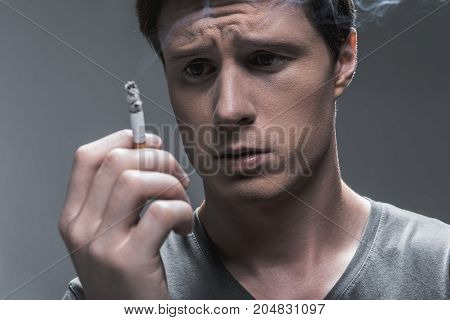 Frustrated male heavy smoker is looking at burning cigarette with doubt. Portrait. Isolated on grey background