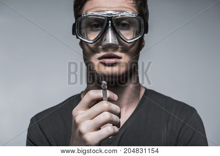 Smoking is dangerous for my health. Portrait of confident young man holding burning cigarette. He is wearing protective mask. Focus on cigarette