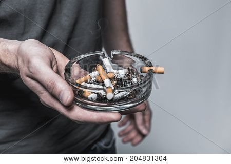 Close up of male hand holding ashtray with cigarette butt. Isolated and copy space in right side
