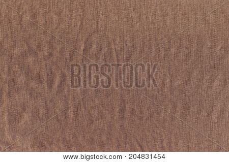 The wrinkled texture of linen cloth brown. Linen fabric