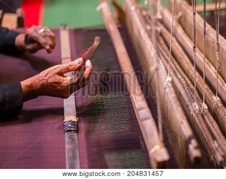 Thai artist demonstrates to make handicraft cloth with local apparatus