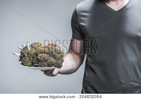Close up of male hand presenting result of smoking on broccoli. Burning cigarettes are inside the vegetable make harm to it
