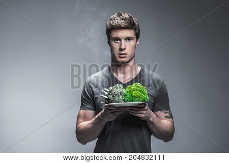 Think about your health. Portrait of serious young man standing and showing plate with broccoli as human lungs. One vegetable with cigarette butts is grey, another is green and healthy. Isolated