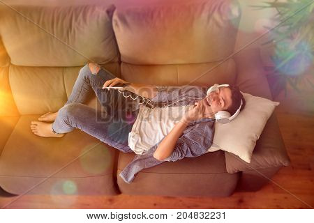 Teen Listening To Music And Dancing On Couch Top View