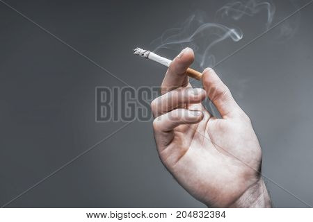 Close up of male hand holding burning cigarette with smoke between fingers. Isolated on grey background. Copy space in left side