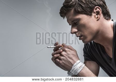 Profile of young guy suffering from nicotine addiction. He is smoking cigarette with tied arms. Guy closed eyes with depression. Isolated and copy space