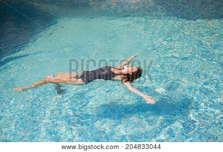 Beautiful girl swimming in the pool on her back.