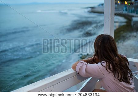 The girl is sitting in a cafe and looking at the sea, a beautiful evening.