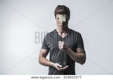 Having social label of alcoholic. Portrait of sad young man with sticker on forehead. He is standing and holding bottle. Isolated and copy space