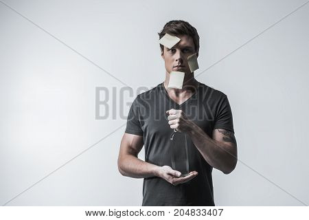 Suffering from social stigma. Depressed young guy is opening bottle of alcohol beverage. He is standing with stickers on his face. Isolated and copy space. Portrait