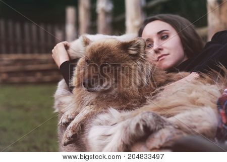 A beautiful woman and her dog nenets shepherd laika sleeping. Hygge style photo