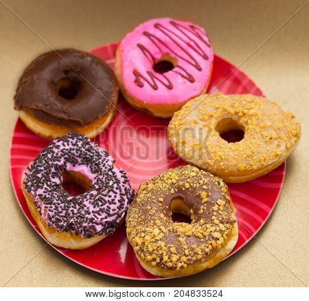 Delicious assorted donuts of different glazed over a red plate in a wooden background.