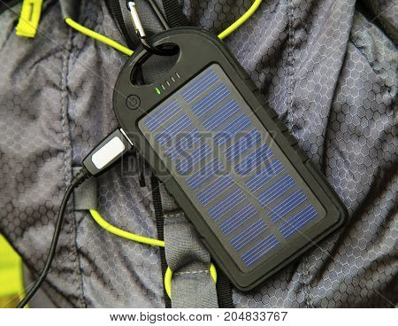Portable solar cell hanging on tourist backpack closeup