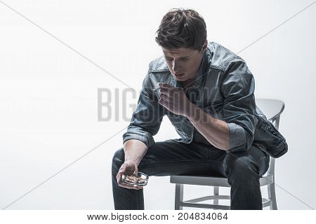 Thoughtful young man is smoking cigarette while sitting on chair. He is holding ashtray. Isolated and copy space