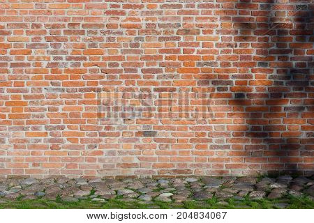 Outdoor Closeup Of Urban Background Combining Red Brick Texture With Line Of Pebbles And Grass Along