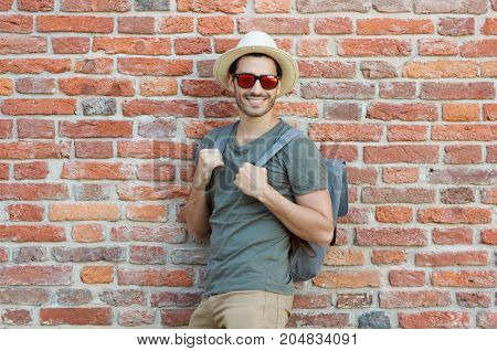 Outdoor Photo Of Young Hipster Guy Standing Against Wall Of Red Bricks With Gray Backpack, Wearing C