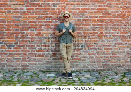 Full-height Portrait Of Young European Male Standing Against Brick Wall, Leaning To It With Backpack