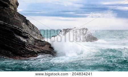 A sea wave breaks on the rock of the coast creating a white foam and water splash.