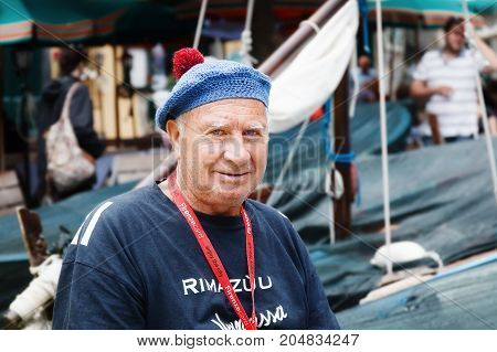 Vernazza (SP) Italy - September 15 2017: Portrait of an old fisherman against the background of boats parked at the small harbor.