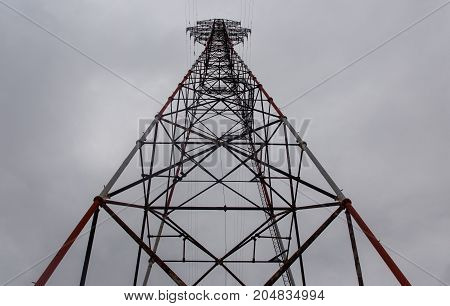 Photo from below of power towers and cloudy cloudy sky