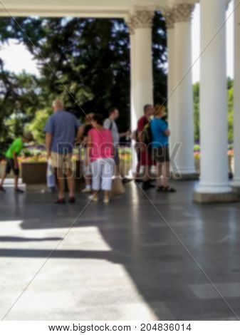 Blured view of tourists at the colonnade with mineral water sources