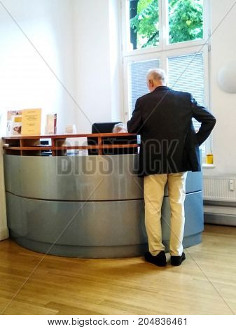 DUSSELDORF GERMANY - AUGUST 8 2017: Unrecognizable old man at reception of a small clinic
