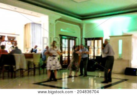 Blurred view of traditional evening dances in lobby of resort spa hotel