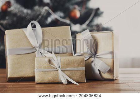 Christmas gifts decorated with silver ribbon on table, closeup, selective focus. Christmas tree background.