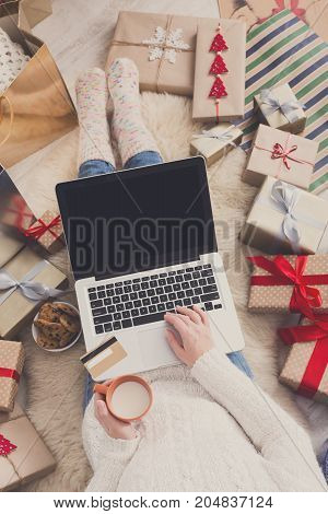 Christmas online shopping top view. Female makes order on laptop with credit card, copy space on screen. Winter holidays sales