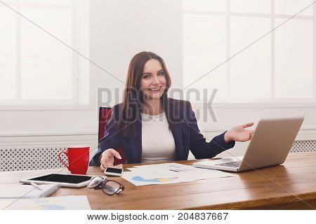 Sucessful project. Happy business woman sitting at table in office and point at laptop, enjoying new achievement.