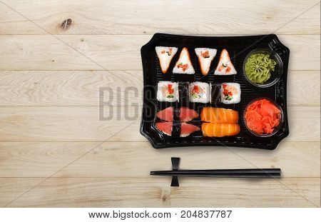 Japanese food delivery. Sushi and rolls top view with copy space on natural wood